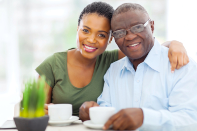 senior man and african nurse smiling at home