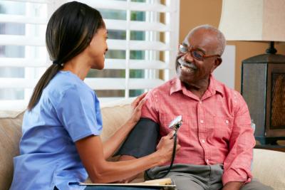Nurse Visiting Senior Male Patient At Home Smiling