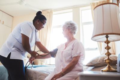 Female nurse doing blood pressure measurement of a senior woman